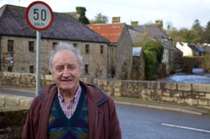 """08 February 2019, Great Britain, Pettigo: Mervyn Johnston, Northern Irish car mechanic, is standing in front of the bridge that connects the Northern Irish part of the village with the Irish part, behind him are houses on the Irish bank of the Termon River. (to dpa """"Bombs and smugglers - how Brexite awakens old fears in Ireland"""") Photo: Christoph Meyer/dpa"""
