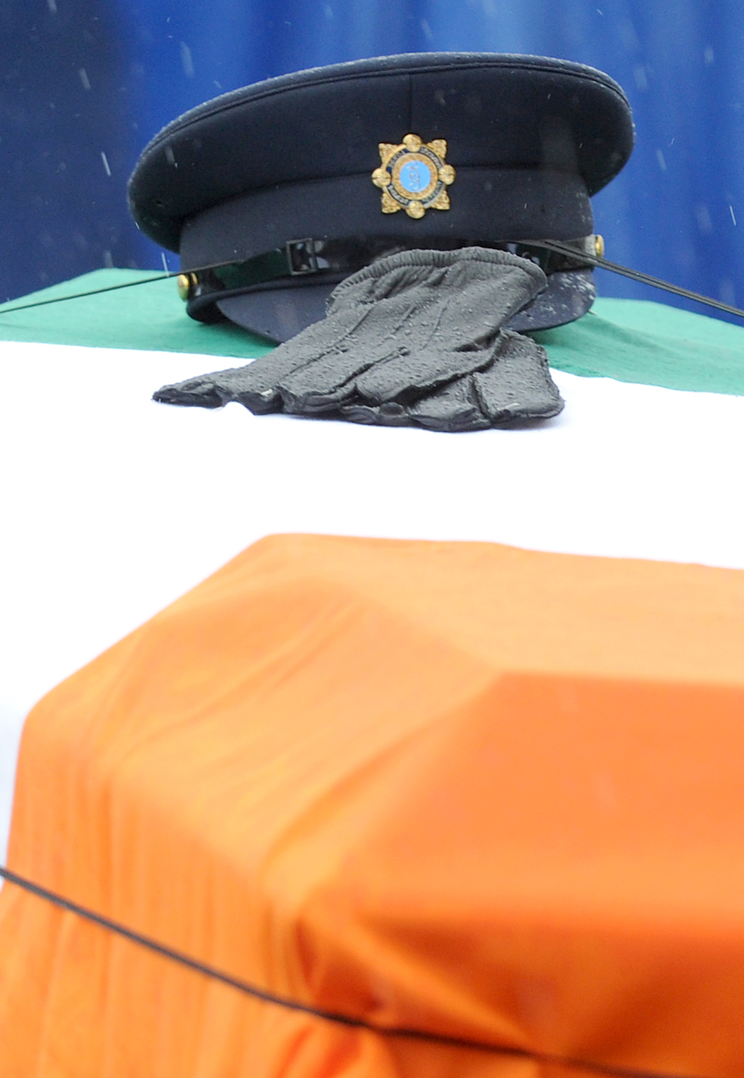 The hat and gloves of murdered Detective Garda Adrian Donohoe rest on his coffin as it arrives at St Joseph's the Redemptorists Church in Dundalk for his funeral mass