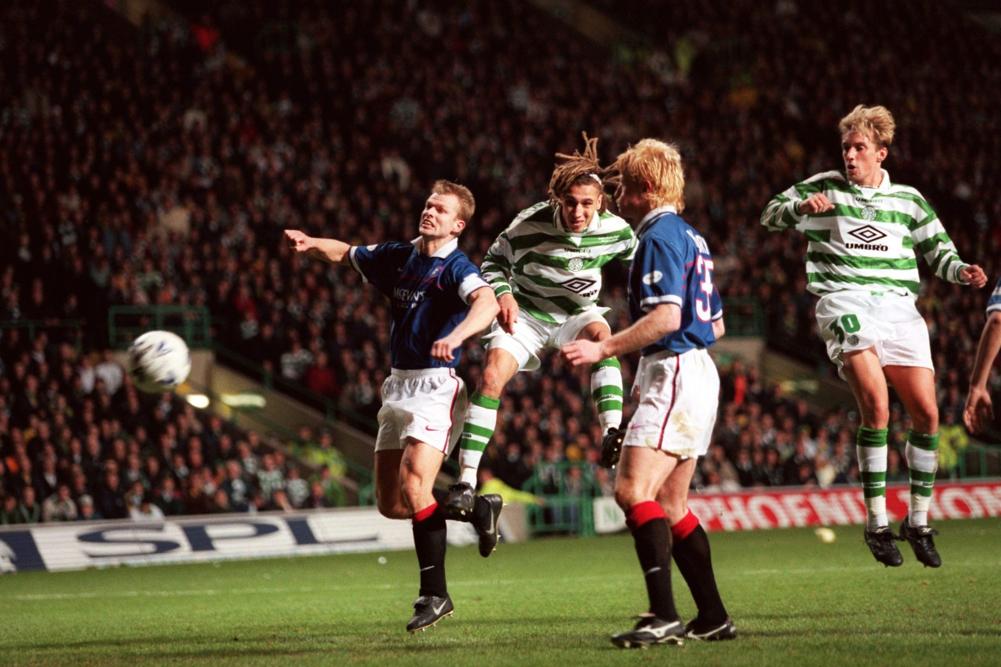 Henrik Larsson of Celtic scores against Rangers