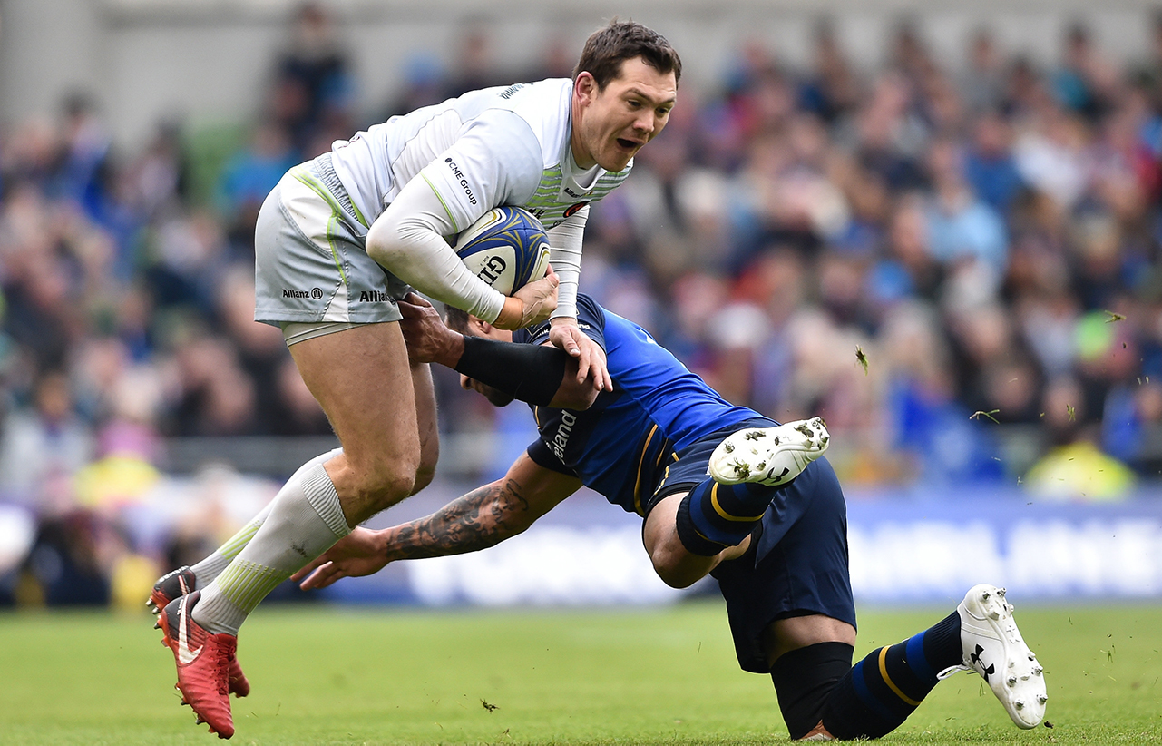 Alex Goode of Saracens is tackled by Isa Nacewa of Leinster during the European Rugby Champions Cup quarter-final match between Leinster and Saracens at the Aviva Stadium