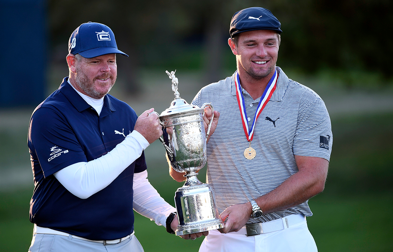 Bryson DeChambeau and his caddie Tim Tucker pose and celebrate with the trophy after winning the U.S. Open golf tournament at Winged Foot Golf Club