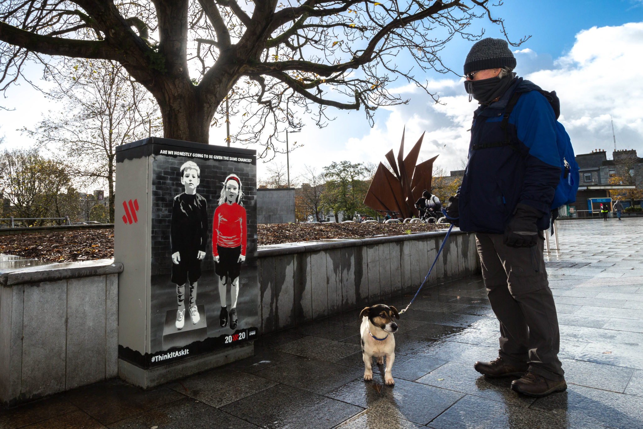 A man and dog pass the mural in Eyre Square.