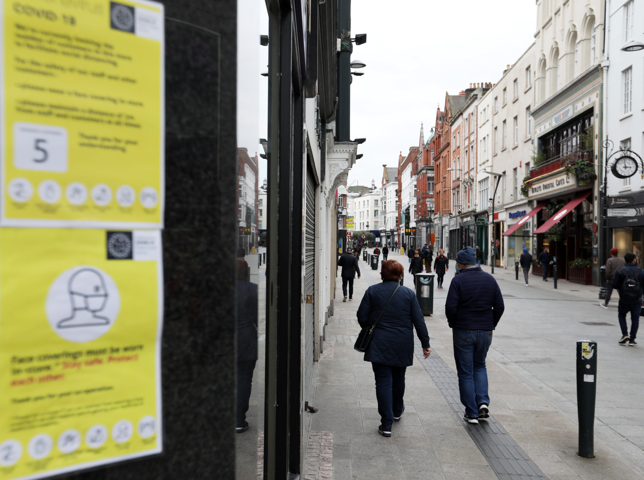 People walking in front of face mask coverings signs on Grafton Street in Dublin