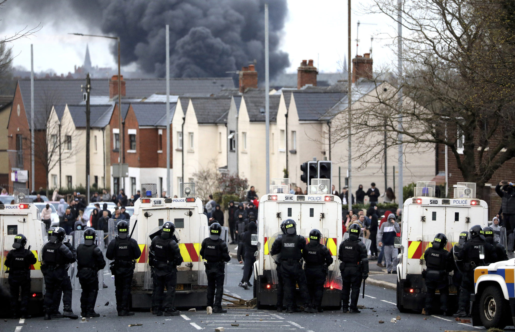 Police form a line on the Springfield road to stop Nationalists and Loyalists attacking each other, as a hijacked bus burns in the distance