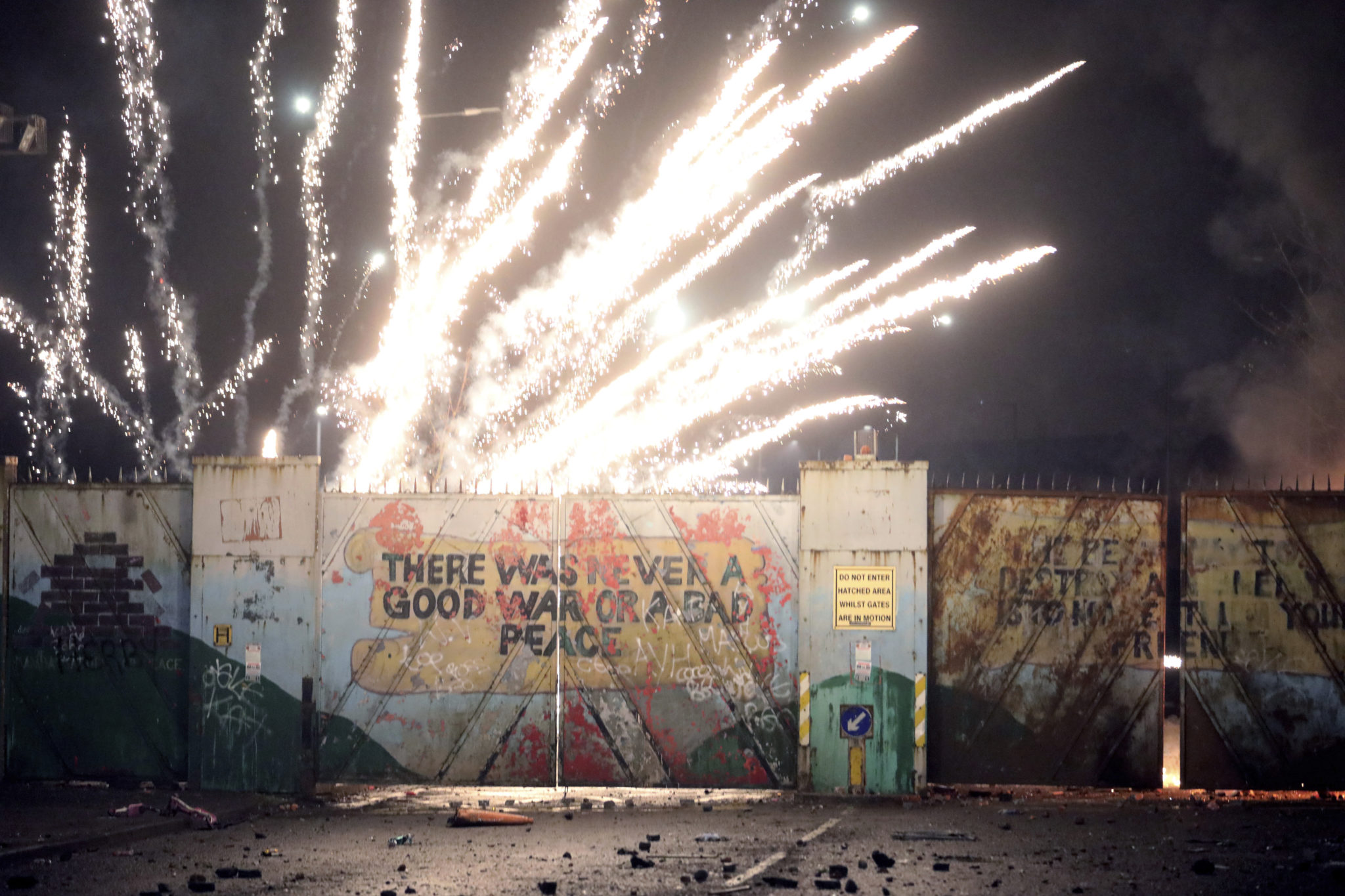 A firework explodes as Nationalists and Loyalists clash with one another at the peace wall on Lanark Way in West Belfast