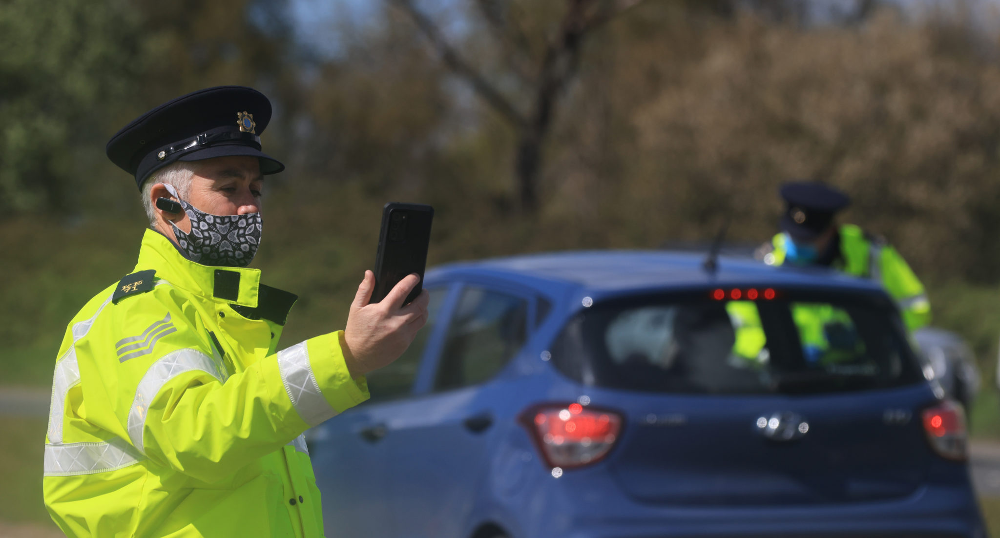 Gardaí at a checkpoint outside Naas, Co Kildare using smartphones running the new Garda Mobility App to detect whether cars are out of insurance.