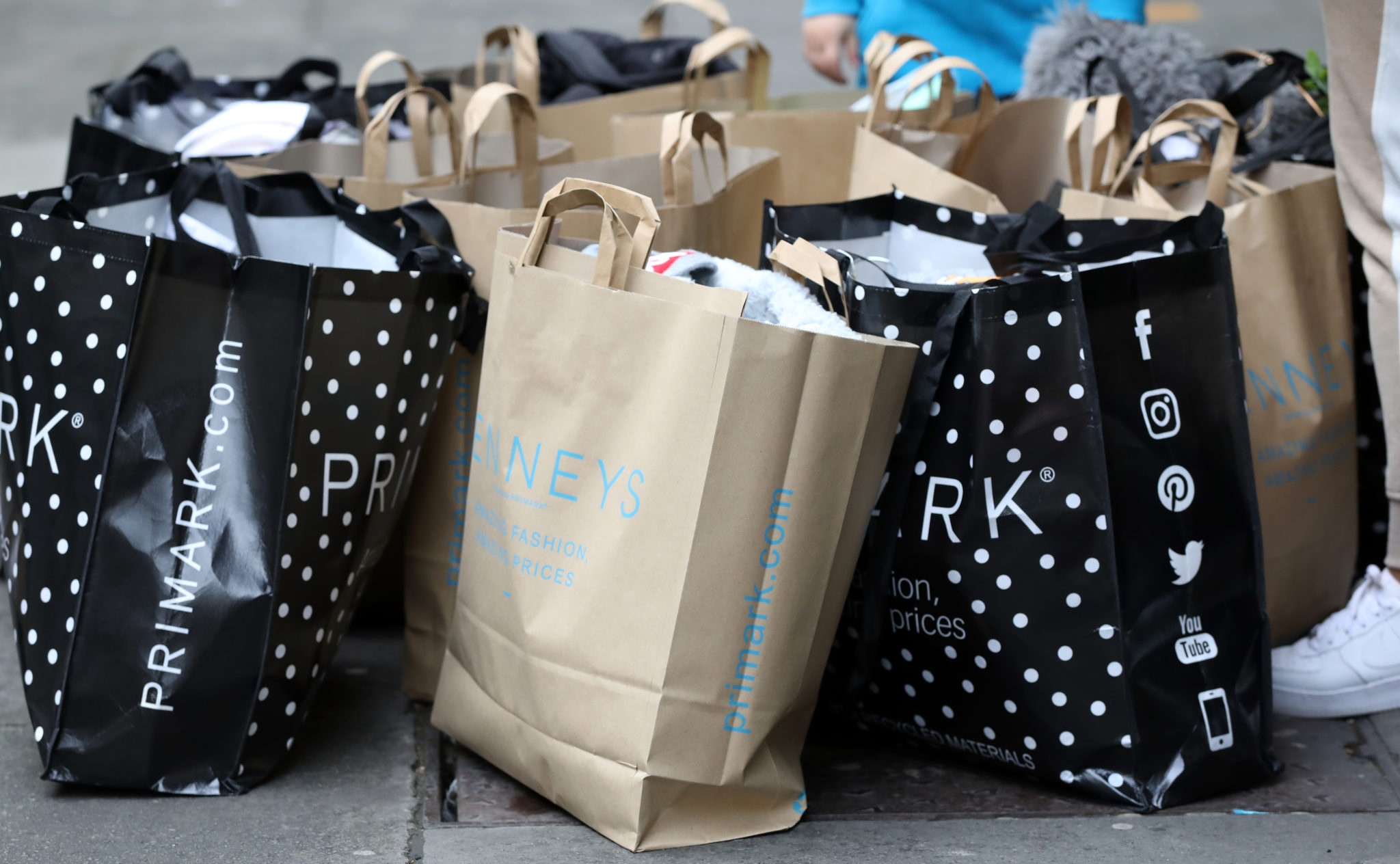 People with shopping bags outside a Penneys store on O'Connell Street in Dublin, on the first day of shops re-opening