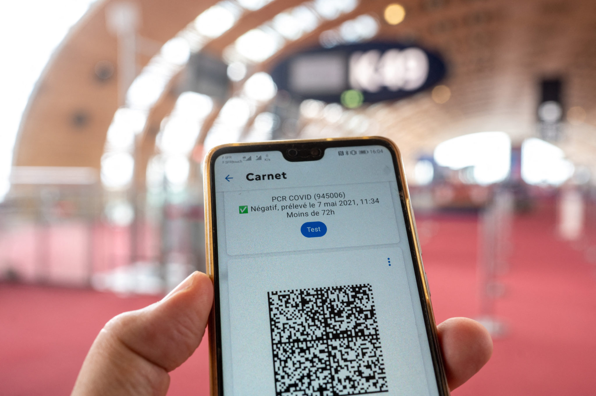 A QR code presenting vaccination certificate, as well as recent PCR test results, is shown on smartphone at Charles de Gaulle Airport in Paris, France.