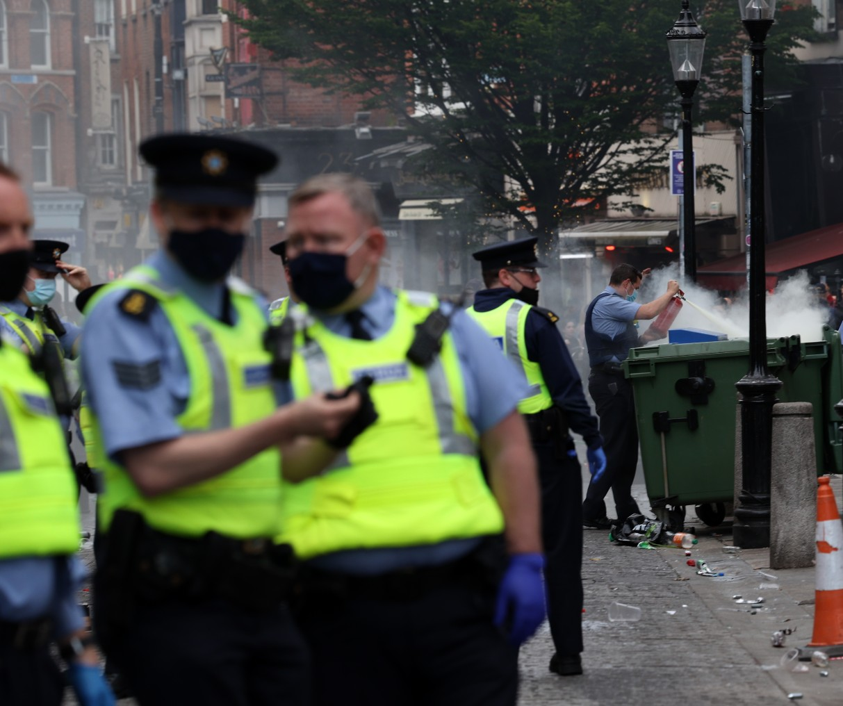 Pictured Members of the An Garda Siochana extinguish a small bin fire on Saturday Night in Dublin