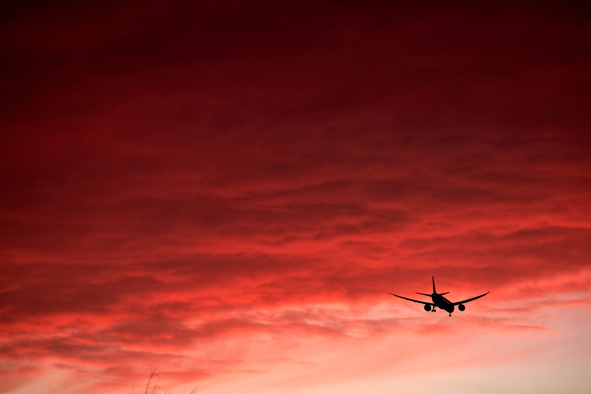 A plane flies under a red sky at sunset in Isleworth, London