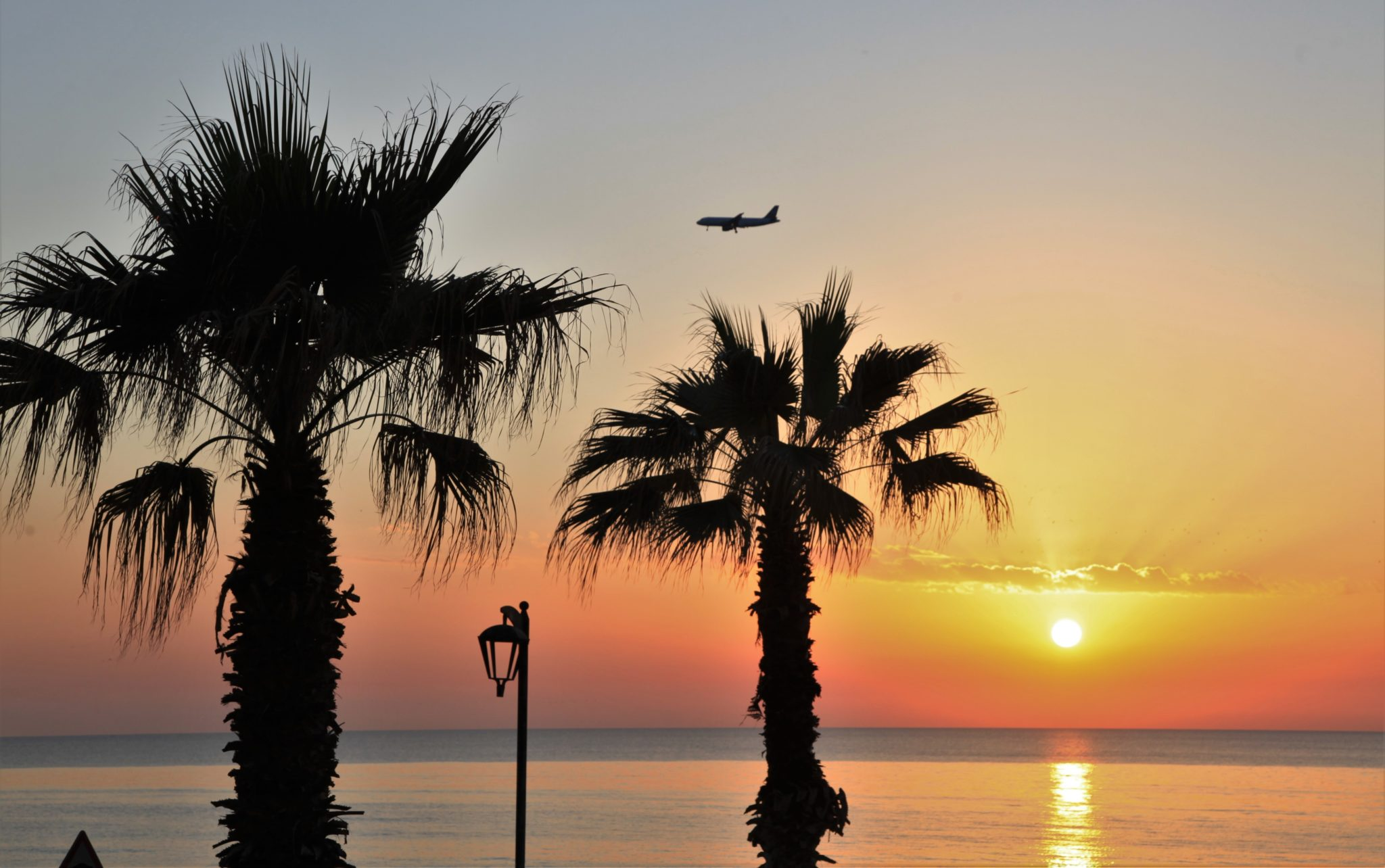 A plane flies over the sea during the sunset in Beirut, Lebanon