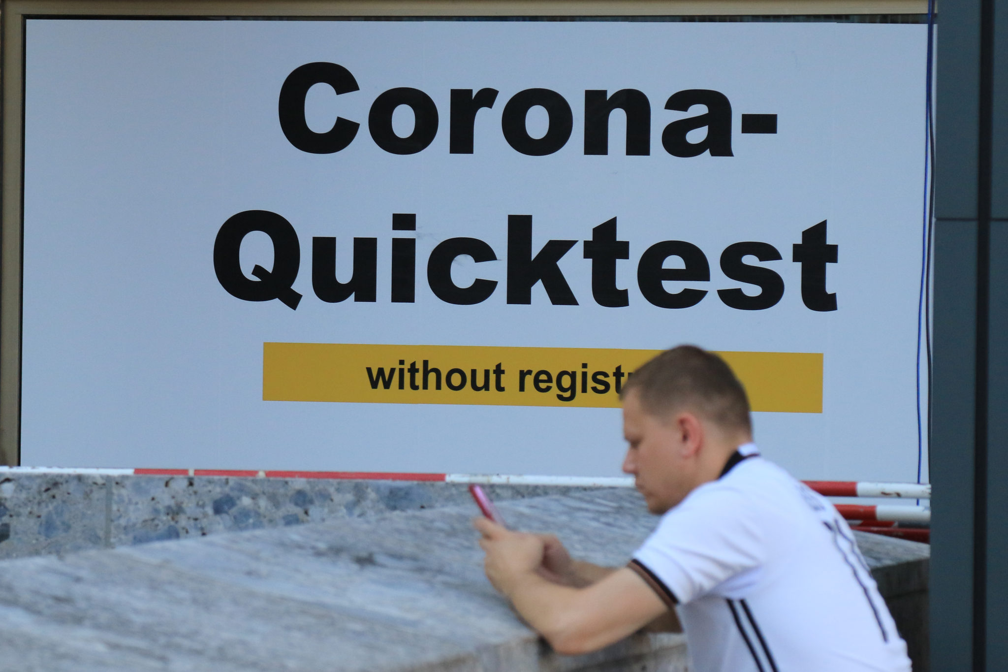 A man in front of Coronavirus Quick Test Station in Munich