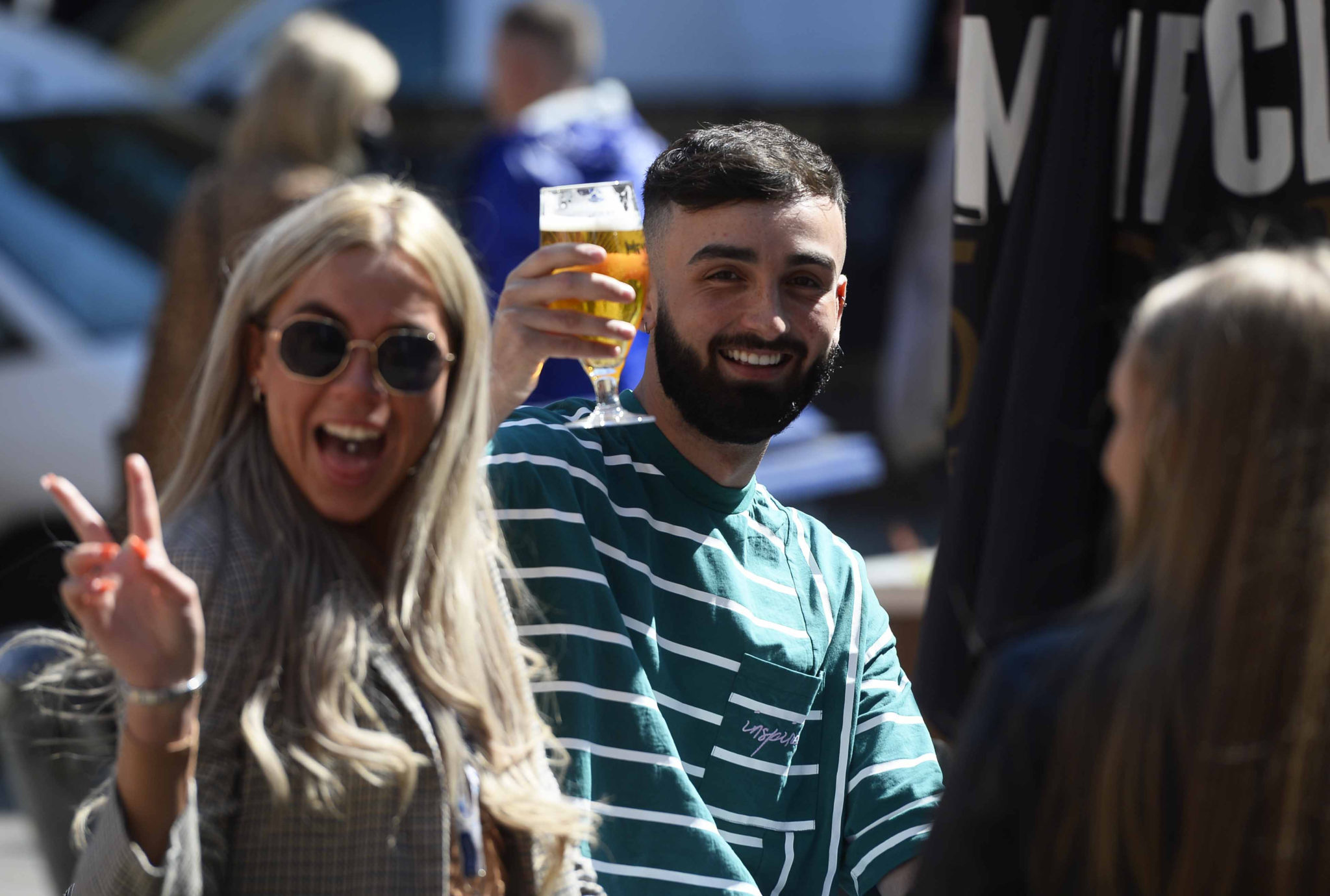 People enjoy a drink at a bar in Belfast,