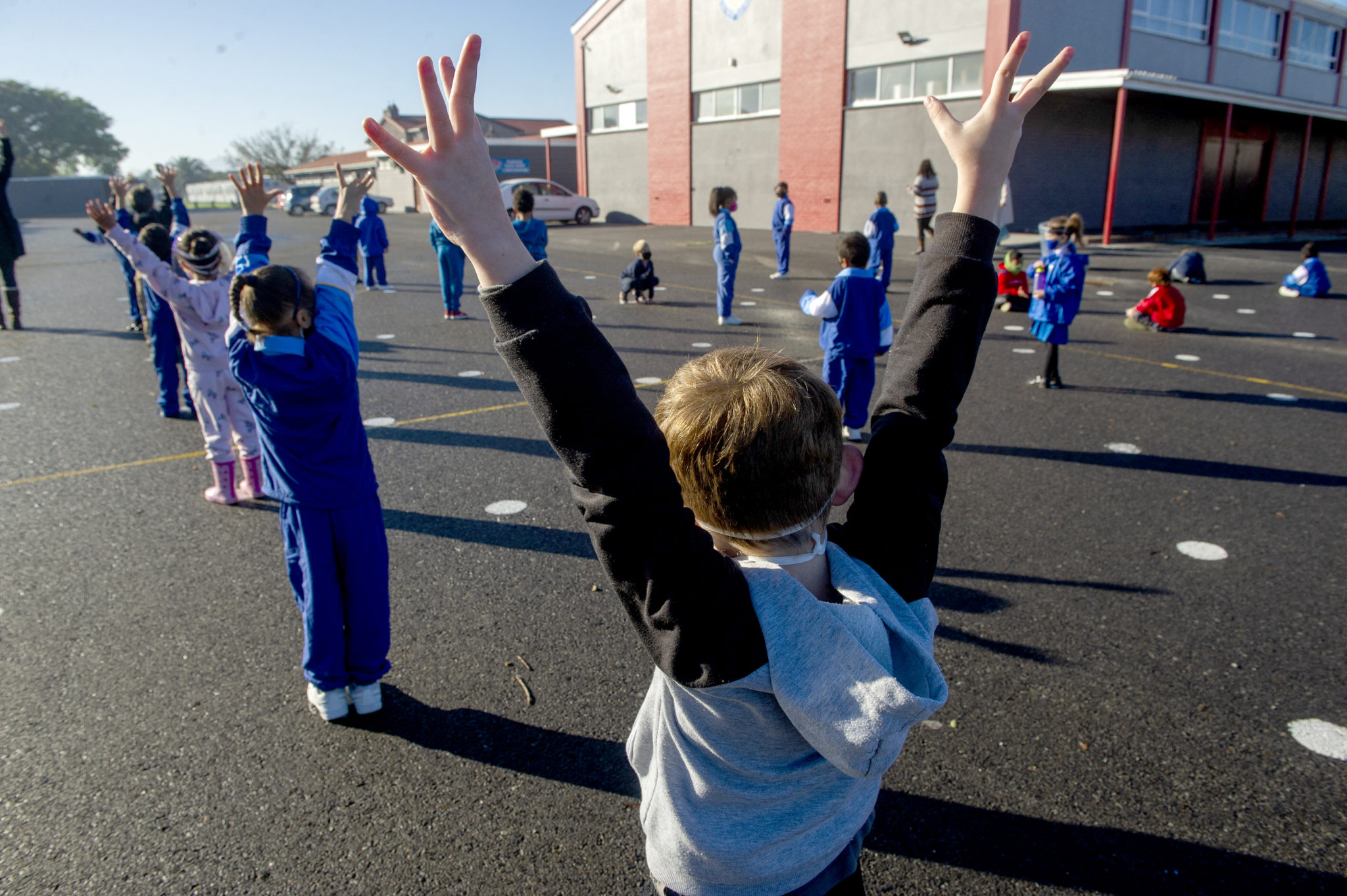 Children stretch during breaktime at a school in Cape Town South Africa