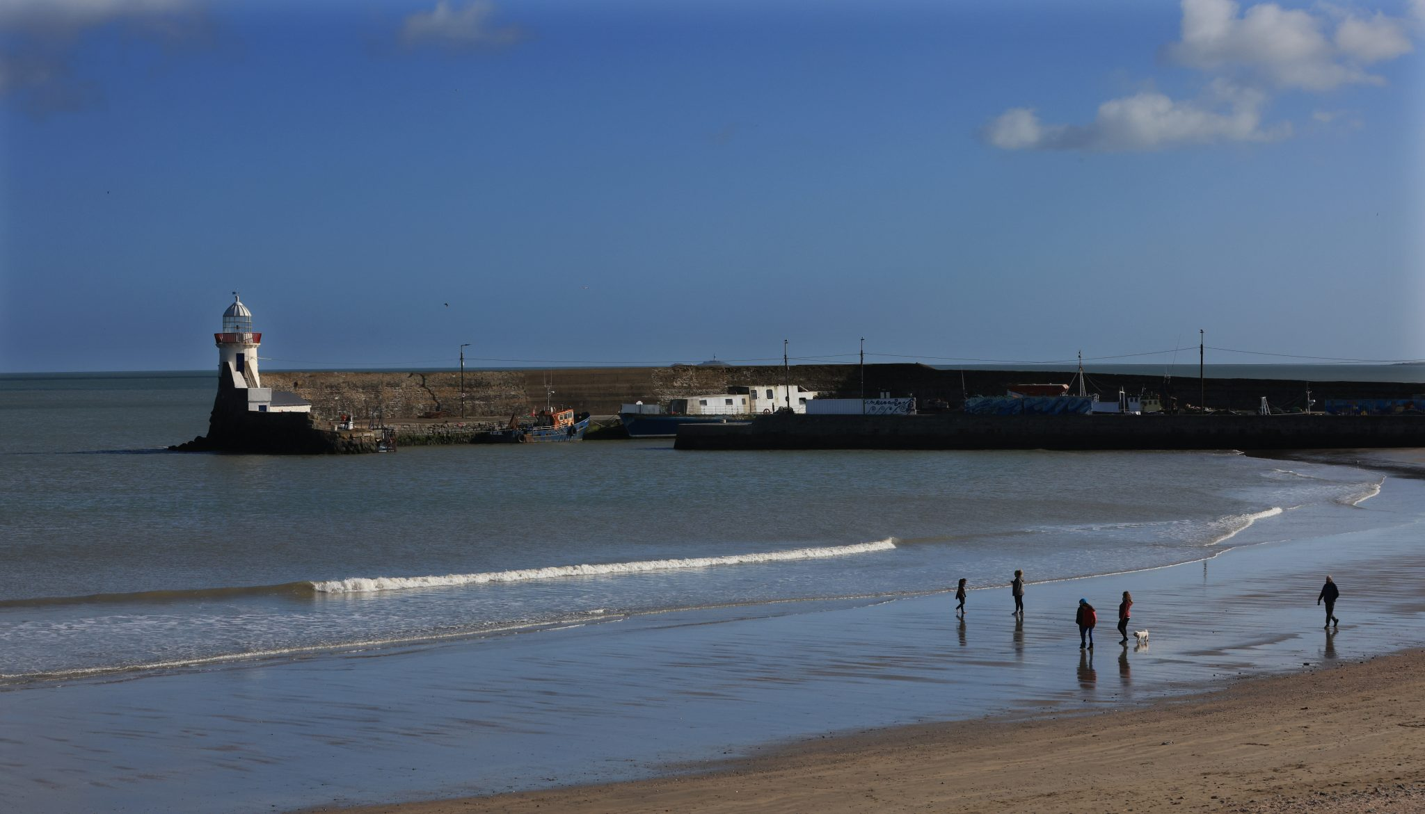 People take advantage of bright, sunny weather beside the sea in Balbriggan in Dublin in February 2021.