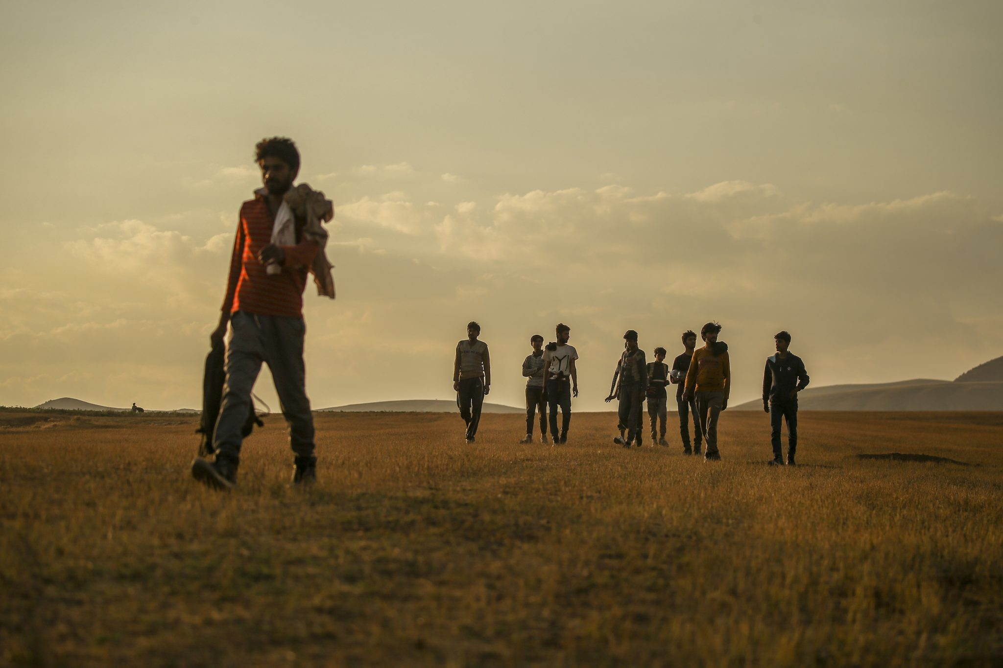 Young men who say they deserted the Afghan military and fled to Turkey through Iran walk in the countryside in Tatvan, eastern Turkey, 17-08-2021. Image: Emrah Gurel/AP/Press Association Images