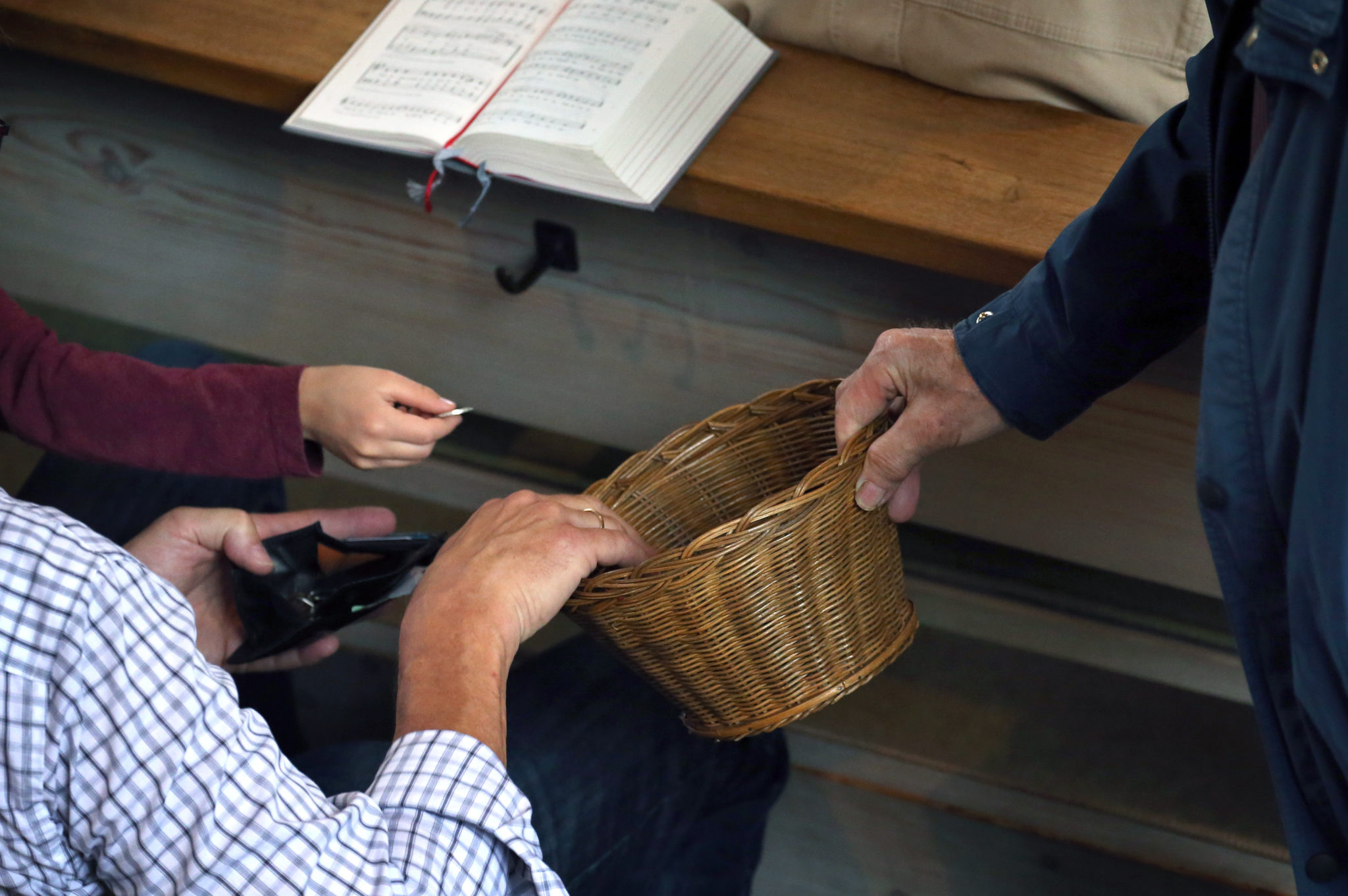 A person donates money into a basket handed around at a Catholic church service in July 2019