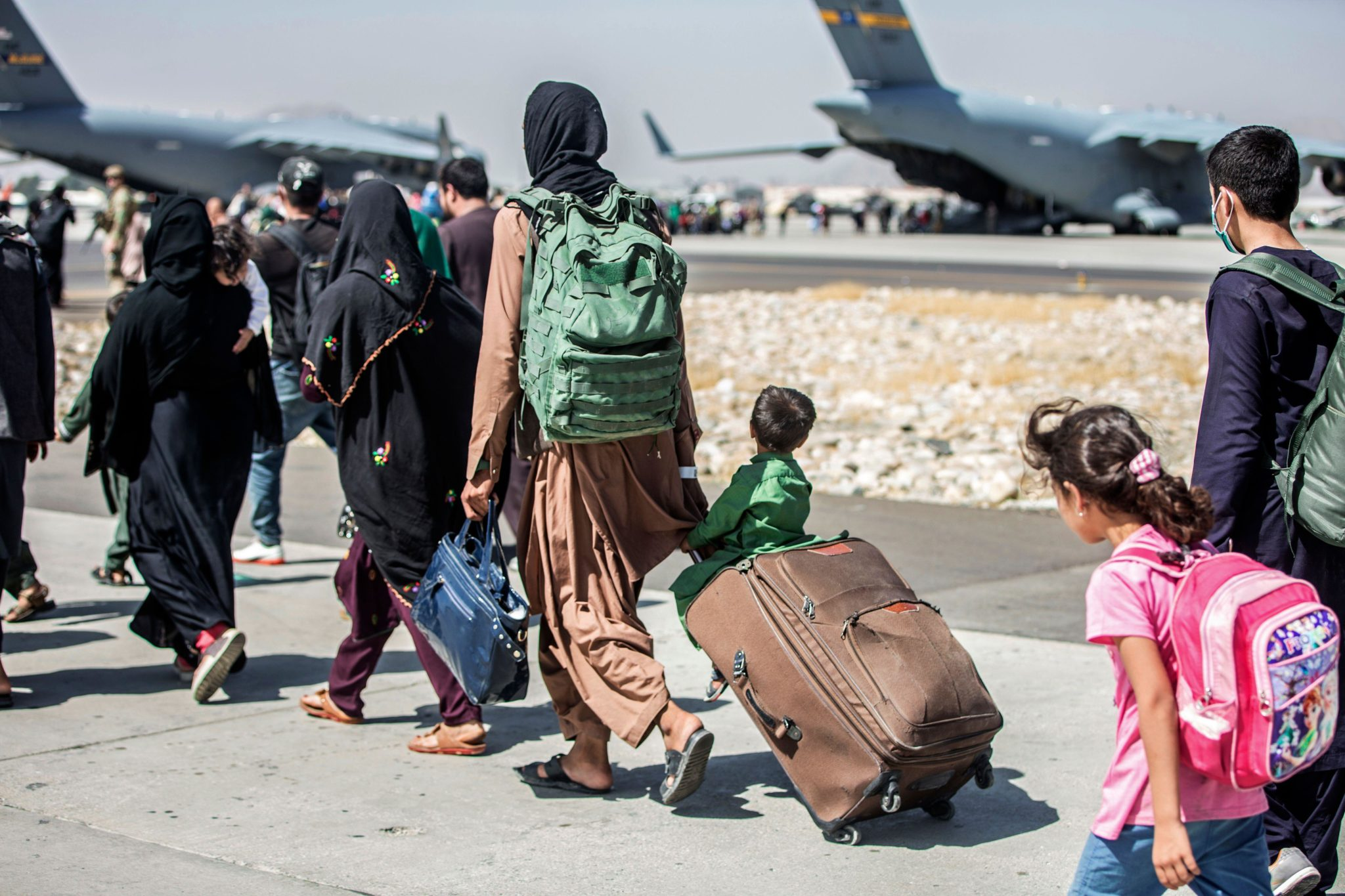 People prepare to board a flight during an evacuation at Hamid Karzai International Airport in Kabul, Afghanistan on August 24th, 2021